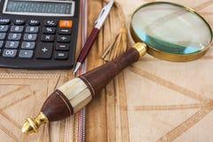 Calculadora, lupa y pluma Foto de archivo
