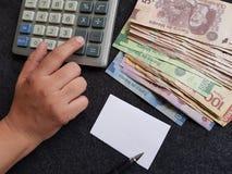 calculadora, mano y cuentas mexicanas en diversas denominaciones Fotografía de archivo libre de regalías