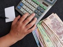 calculadora, mano y cuentas mexicanas en diversas denominaciones Fotos de archivo libres de regalías