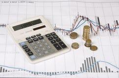 Calculadora, monedas, pluma en gráfico económico Fotos de archivo