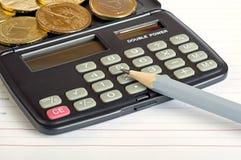 Calculadora, monedas y lápiz Foto de archivo