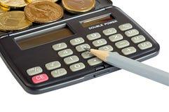 Calculadora, monedas y lápiz Fotos de archivo libres de regalías