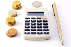 Calculadora, monedas y pluma Imágenes de archivo libres de regalías
