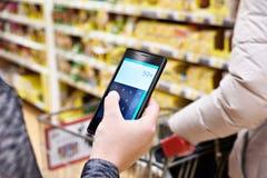 Calculadora na tela do smartphone à disposição de clientes das mulheres Fotografia de Stock