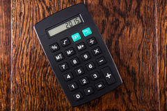 Calculadora negra en el escritorio de madera imagen de archivo