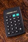 Calculadora negra en el escritorio de madera Foto de archivo libre de regalías
