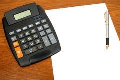 Calculadora, papel, pluma Imagenes de archivo