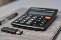 A calculadora, a pena e o usb colam no escritório Fotos de Stock