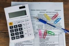 Calculadora, pluma, documento y clips fotografía de archivo libre de regalías