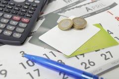 Calculadora, pluma, monedas y tarjetas de crédito en un calendario Imagen de archivo