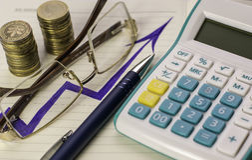 Calculadora, pluma, vidrios y monedas Imágenes de archivo libres de regalías