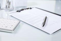 Calculadora, pluma y documentos en un escritorio Imagen de archivo libre de regalías