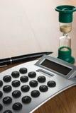 Calculadora, pluma y reloj de arena en el sol de la mañana fotos de archivo libres de regalías