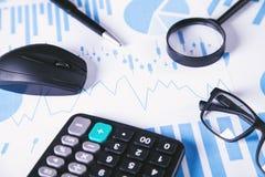 Calculadora, pluma y vidrios con los gráficos financieros imagen de archivo