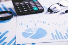 Calculadora, pluma y vidrios con los gráficos financieros fotos de archivo libres de regalías