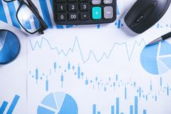 Calculadora, pluma y vidrios con los gráficos financieros fotografía de archivo