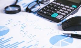 Calculadora, pluma y vidrios con los gráficos financieros fotos de archivo