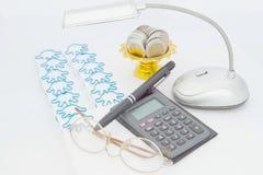 Calculadora preta com vidros e moedas na bandeja com suporte Fotos de Stock
