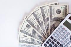 Calculadora que miente en cuentas de dólar americano en un fondo blanco, dinero imágenes de archivo libres de regalías