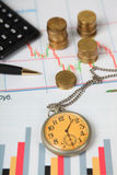 Calculadora, reloj y pilas de monedas Imagenes de archivo