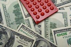 Calculadora roja en el fondo de $100 billetes de banco. Fotografía de archivo