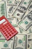 Calculadora roja en el fondo de $100 billetes de banco Fotos de archivo libres de regalías