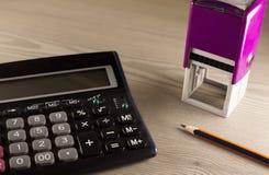 Calculadora, sello y lápiz Imagen de archivo libre de regalías