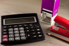Calculadora, selo, grampeador e lápis fotografia de stock