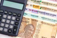 Calculadora sobre de billetes de banco del indio 10, 50, 100, 200, 500 y 2000 rupias a estrenar Fondo colorido del dinero