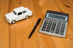 Calculadora, una pluma y un coche del juguete Imagen de archivo libre de regalías