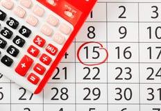 Calculadora vermelha em calendário marcado foto de stock