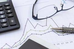 Calculadora, vidrios, pluma, teléfono móvil y carta financiera, busi Imagen de archivo libre de regalías