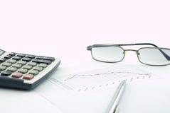 Calculadora, vidrios, pluma y gráfico foto de archivo