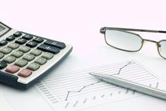 Calculadora, vidrios, pluma y gráfico de la posición fotografía de archivo libre de regalías