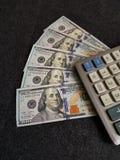 calculadora y 100 billetes de dólar Foto de archivo libre de regalías