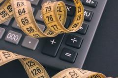 Calculadora y cinta métrica amarilla Imágenes de archivo libres de regalías