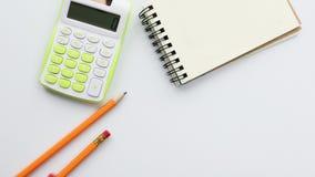 Calculadora y cuaderno en el escritorio, l?pices m?viles