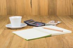 Calculadora y cuaderno en la tabla de madera Imágenes de archivo libres de regalías