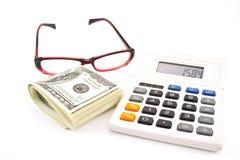 Calculadora y dólares y vidrios Imagen de archivo