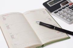 Calculadora y diario del asunto con la pluma Imagenes de archivo