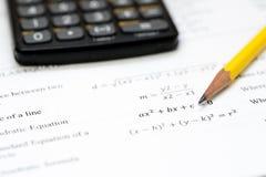 Calculadora y lápiz en un fondo blanco con el mathem Fotografía de archivo