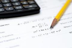 Calculadora y lápiz en un fondo blanco con el mathem Foto de archivo