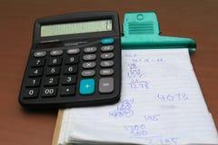 Calculadora y libro con el número al azar escrito Foto de archivo libre de regalías