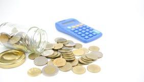 Calculadora y moneda en el fondo blanco Imagen de archivo