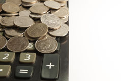 Calculadora y moneda en el fondo blanco Foto de archivo libre de regalías