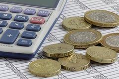 Calculadora y monedas en una hoja de balance Fotos de archivo libres de regalías