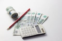 Calculadora y mucho dinero en un fondo blanco Foto de archivo libre de regalías