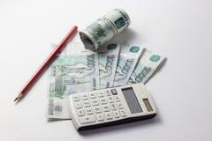 Calculadora y mucho dinero en un fondo blanco Fotografía de archivo libre de regalías