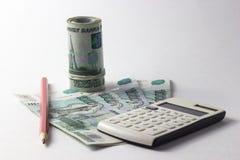 Calculadora y mucho dinero en un fondo blanco Imagen de archivo libre de regalías