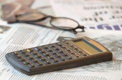 Calculadora y periódico del asunto Imagenes de archivo